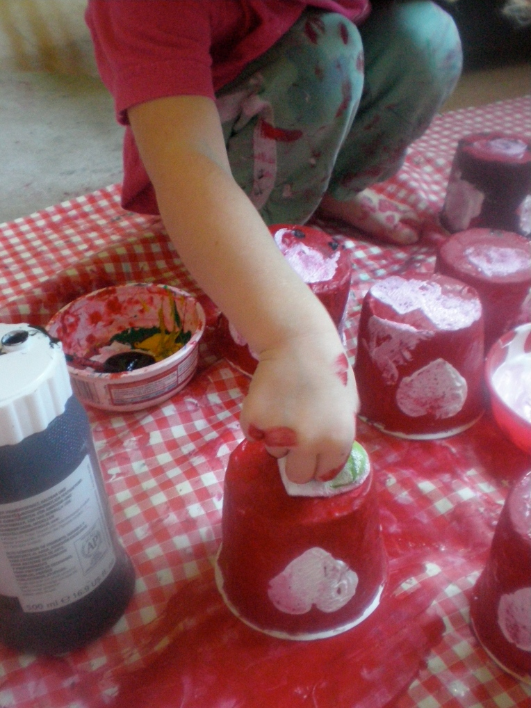 child printing pattern on papier mache pots